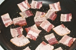 Chopped Bacon crisping with freshly ground peppercorns